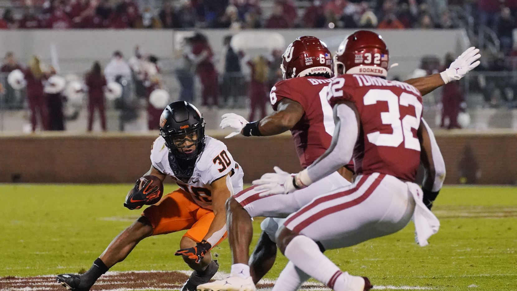 Oklahoma State running back Chuba Hubbard (30) slips in front of Oklahoma cornerback Tre Brown (6) and safety Delarrin Turner-Yellan (32) during the first half of an NCAA college football game in Norman, Okla., Saturday, Nov. 21, 2020. (AP Photo/Sue Ogrocki)