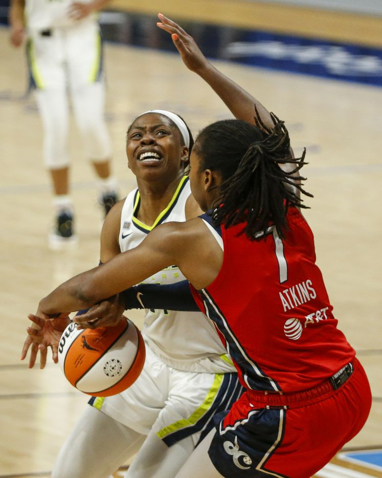 Dallas Wings guard Arike Ogunbowale (24) is fouled driving to the basket by Washington Mystics guard Ariel Atkins (7) during the fourth quarter at College Park Center on Saturday, June 26, 2021, in Arlington. (Elias Valverde II/The Dallas Morning News)