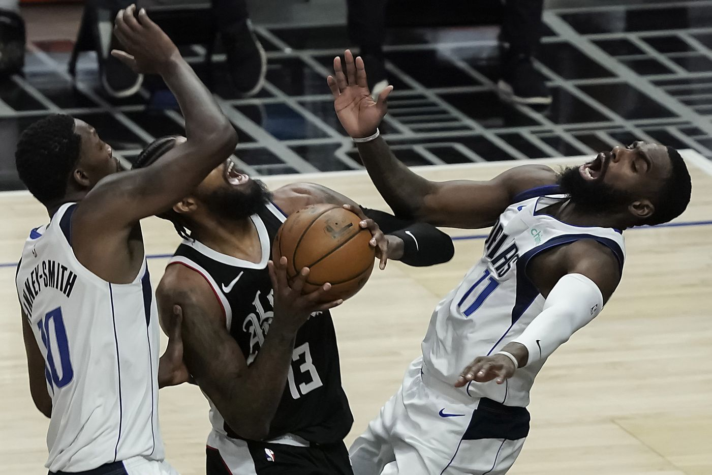 Dallas Mavericks forward Tim Hardaway Jr. (11) draws a charge from LA Clippers guard Paul George (13) during the second half of an NBA playoff basketball game at Staples Center on Saturday, May 22, 2021, in Los Angeles. The Mavericks won the game 113-103.