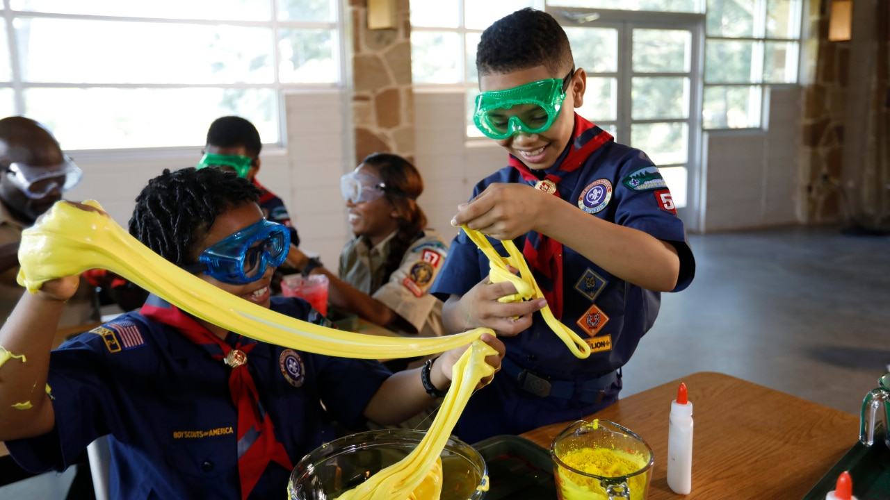 A group of scouts wearing uniforms and eye protection participates in a science experiment.