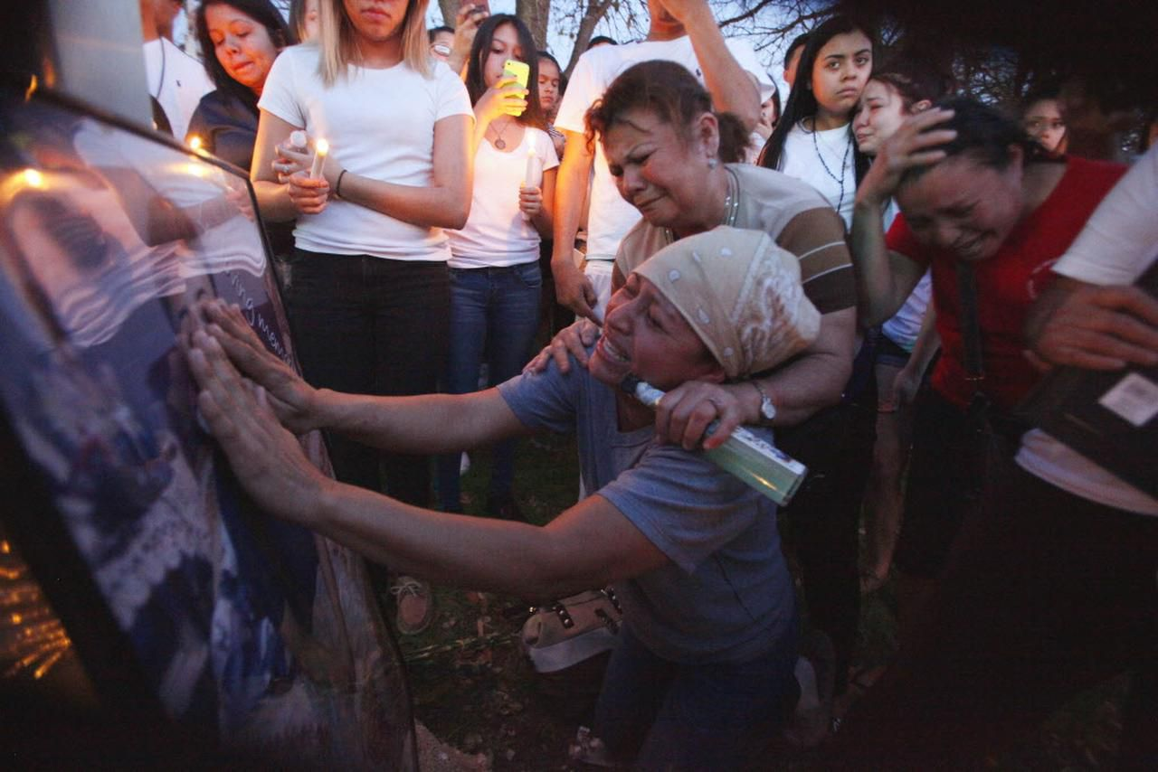Ana Henriquez toca un cuadro con la imagen de su hijo José Cruz de 16, el jovencito de 16 años que murió cuando fue baleado por un agente de la policía de Farmers Branch que estaba fuera de servicio el domingo por la noche en Addison. Norma Velazquez, amiga de Henriquez la consola. (ESPECIAL PARA AL DIA/BEN TORRES)