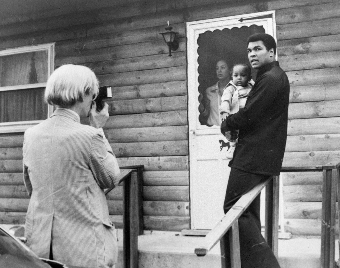 In this Thursday, Aug. 18, 1977 file photo, artist Andy Warhol, left, photographs Muhammad Ali, his infant daughter, Hanna, and wife, Veronica, at Ali's training camp in Deer Lake, Pa.