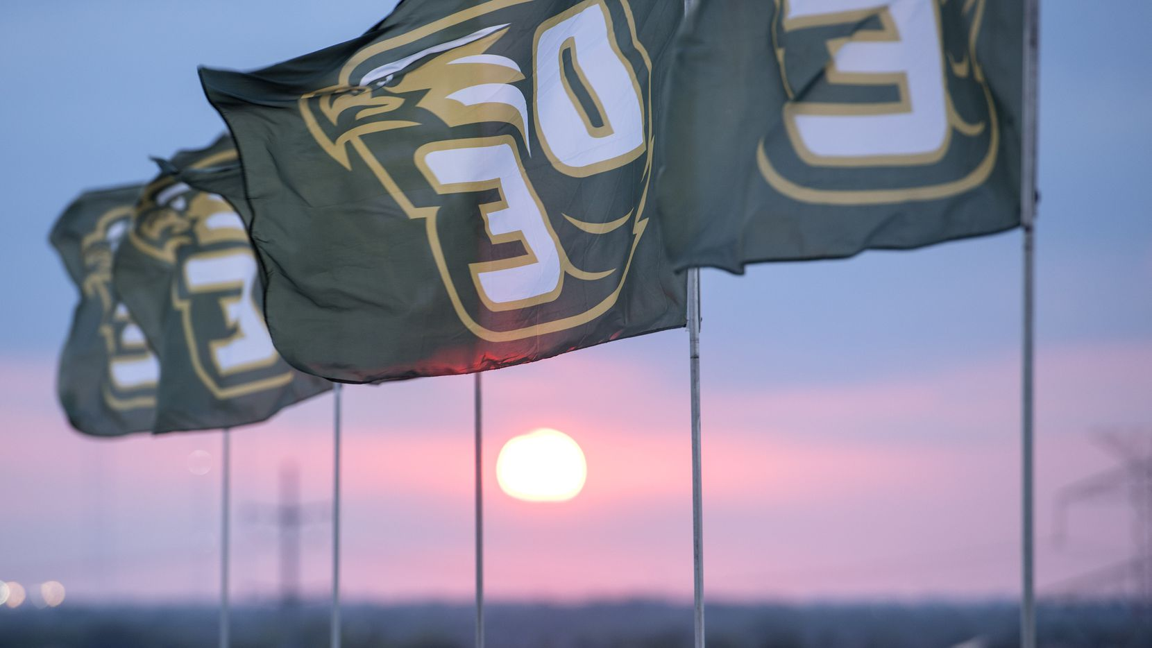 DeSoto flags fly as the sun sets before the start of a high school football game against Denton Guyer at Eagle Stadium in DeSoto, Texas, Friday, September 2, 2016. (Jeffrey McWhorter/Special Contributor)
