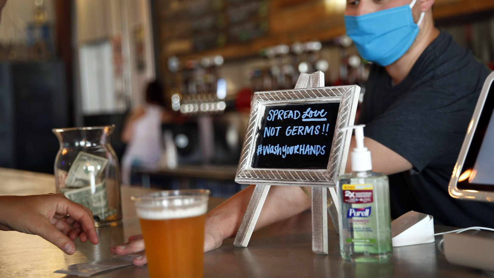 Patrons return to the Legal Draft in Arlington, Texas with a bar sign reminding them to please wash their hands as they've been allowed to reopen, Friday, May 22 2020, during the COVID-19 pandemic. (Tom Fox/The Dallas Morning News)