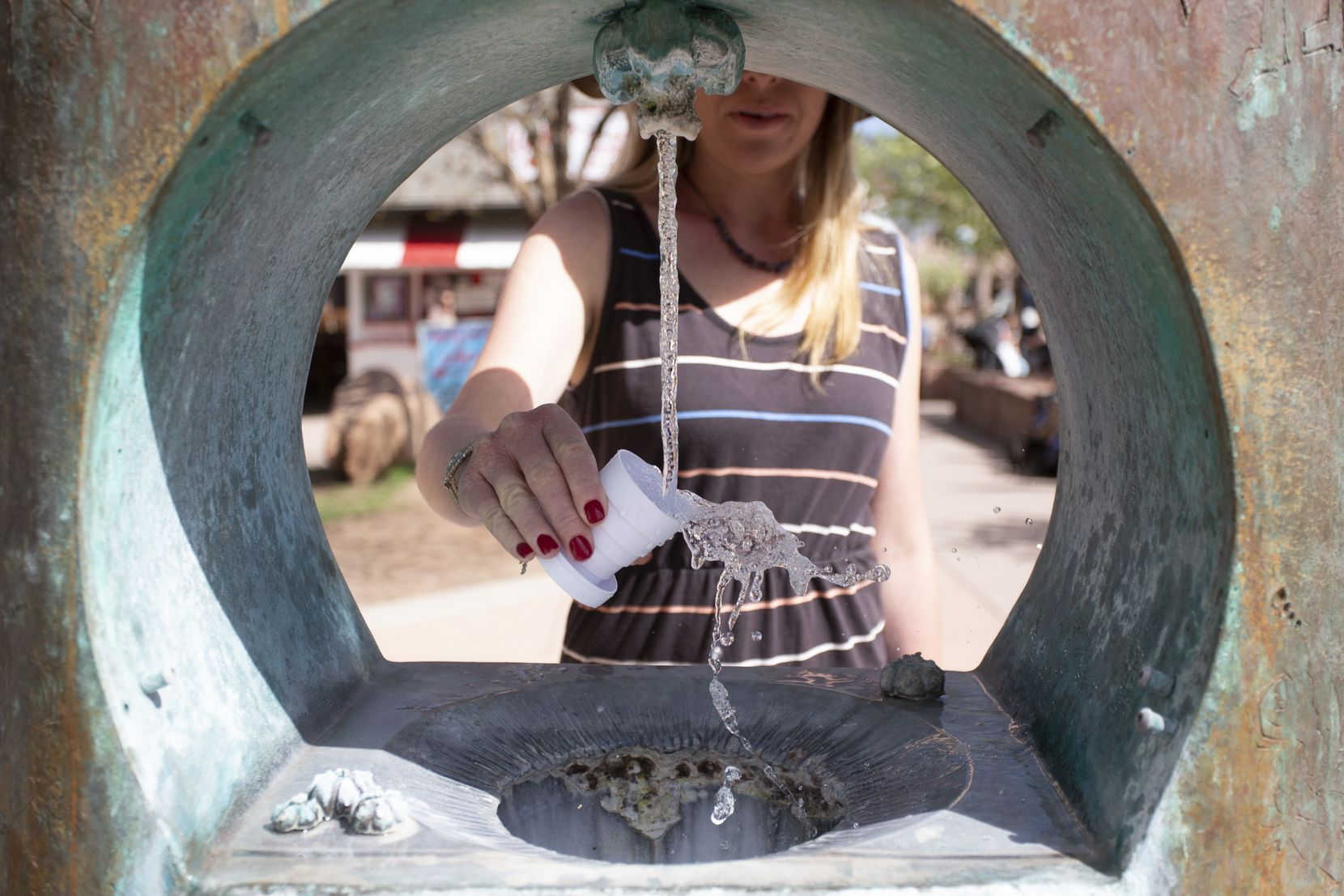 A woman samples the water from one of the eight mineral springs that feed into Manitou Springs, Colo.