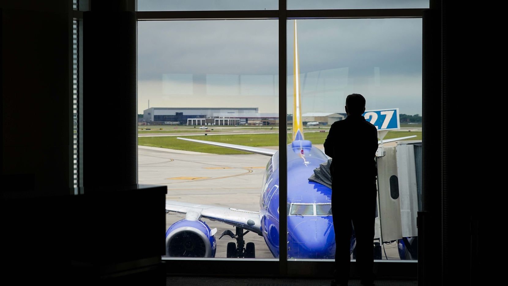 A man looks out over a Southwest Airlines 737 parked at a gate at Houston Hobby Airport.