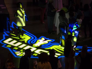 Fans walk across the floor of the arena during the Dallas Wings WNBA draft night party at College Park Center on the campus of the University of Texas at Arlington on Thursday, April 14, 2016, in Arlington.