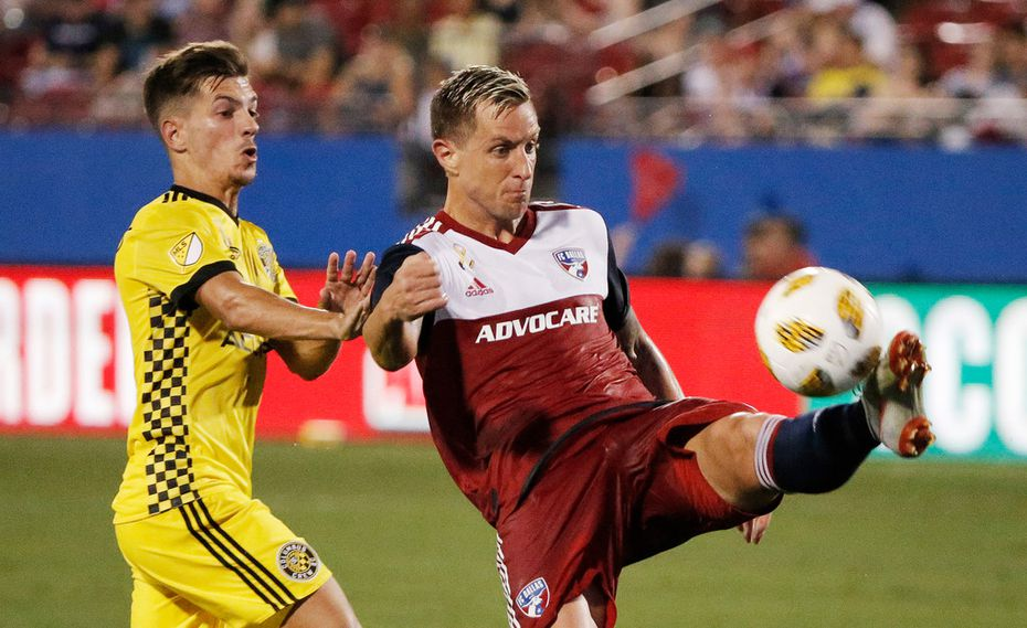 FC Dallas defender Reto Ziegler, right, plays the ball away from Columbus Crew midfielder Pedro Santos, left, during the first half of an MLS soccer match, Saturday, Sept. 15, 2018, in Frisco, Texas. (AP Photo/Brandon Wade)