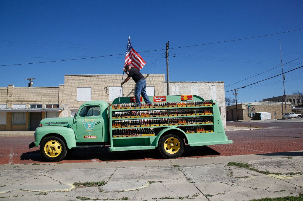 Dublin Bottling Works employee Charles Ditmore puts up one of the American flags on the old display truck outside the facility in Dublin. (Guy Reynolds/The Dallas Morning News)