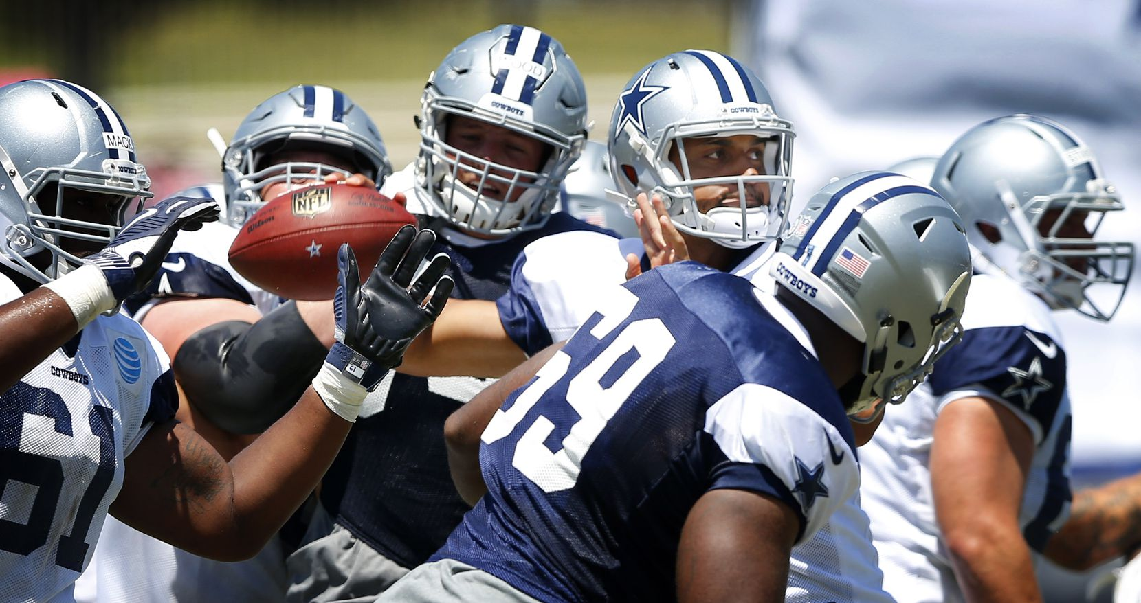 Dallas Cowboys quarterback Dak Prescott (4) cocks the ball back for a pass as he is surrounded by teammates during morning practice at training camp in Oxnard, California, Thursday, August 11, 2016. (Tom Fox/The Dallas Morning News)