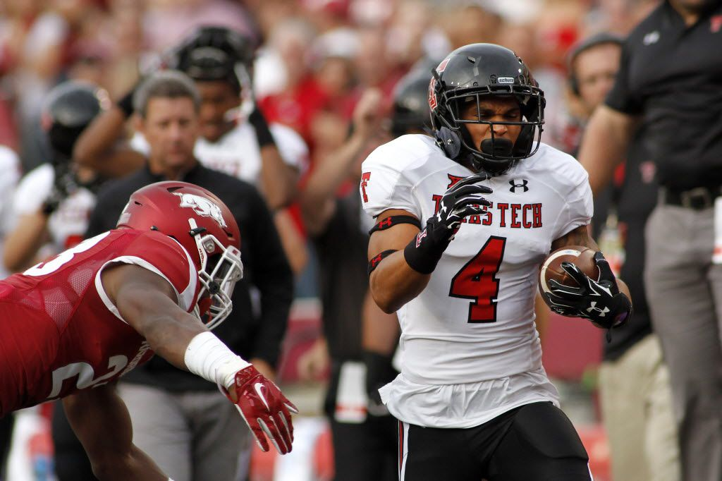 Arkansas' Dre Greenlaw, left, lunges after Texas Tech's Justin Stockton (4) during the first half of an NCAA college football game, Saturday, Sept. 19, 2015, in Fayetteville, Ark. (AP Photo/Samantha Baker) 09202015xPUB