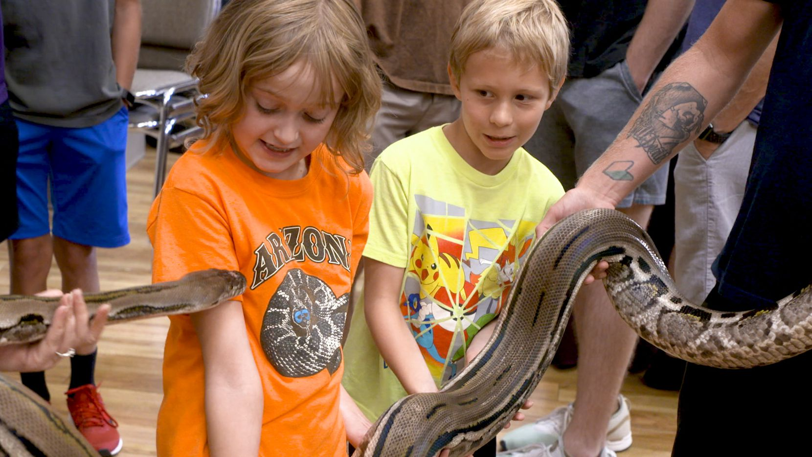 Reghan Reeves and Cayman Jones hold a dwarf reticulated python at Repticon in Grapevine in August.