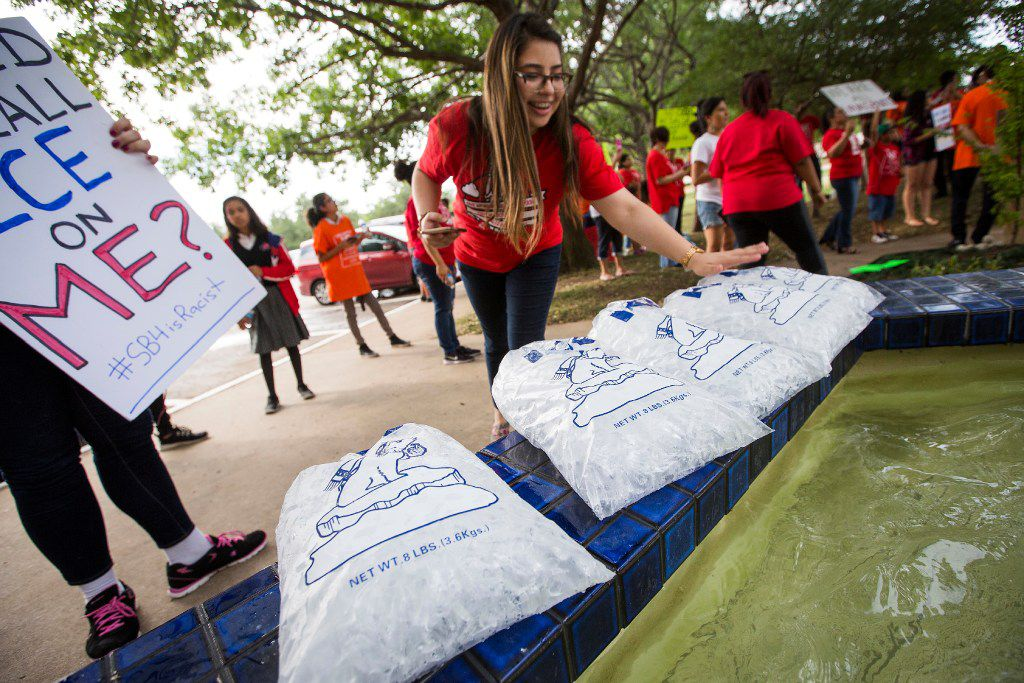 """Opponents of the SB 4 law, Texas' """"sanctuary cities"""" legislation, set out bags of ice as they rallied outside the  offices of state Rep. Matt Rinaldi on Wednesday in Farmers Branch.  Rinaldi's claim that he called ICE agents on protesters at the state Capitol complaining about SB 4 sparked a scuffle on the floor of the Legislature last week."""