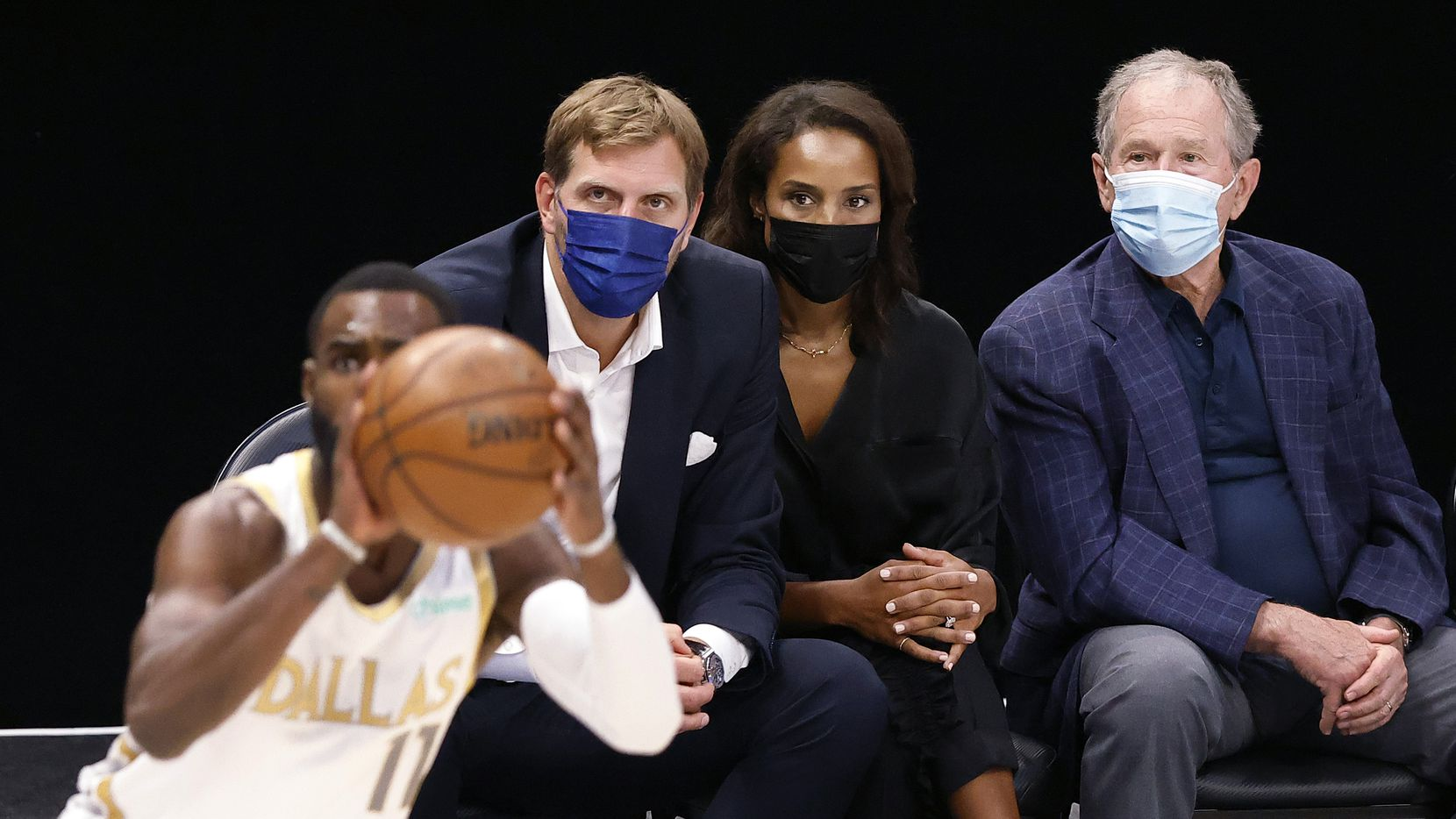 Former Dallas Maverick Dirk Nowitzki (left) and his wife Jessica joined former President George W. Bush in court side seats for the Dallas Mavericks-Brooklyn Nets game at the American Airlines Center in Dallas, Thursday, May 6, 2021.