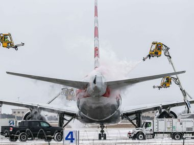 An American Airlines jet is de-iced at DFW International Airport before takeoff as winter flurries arrive in Irving on Sunday, February 14, 2021 ahead of major snowstorm.