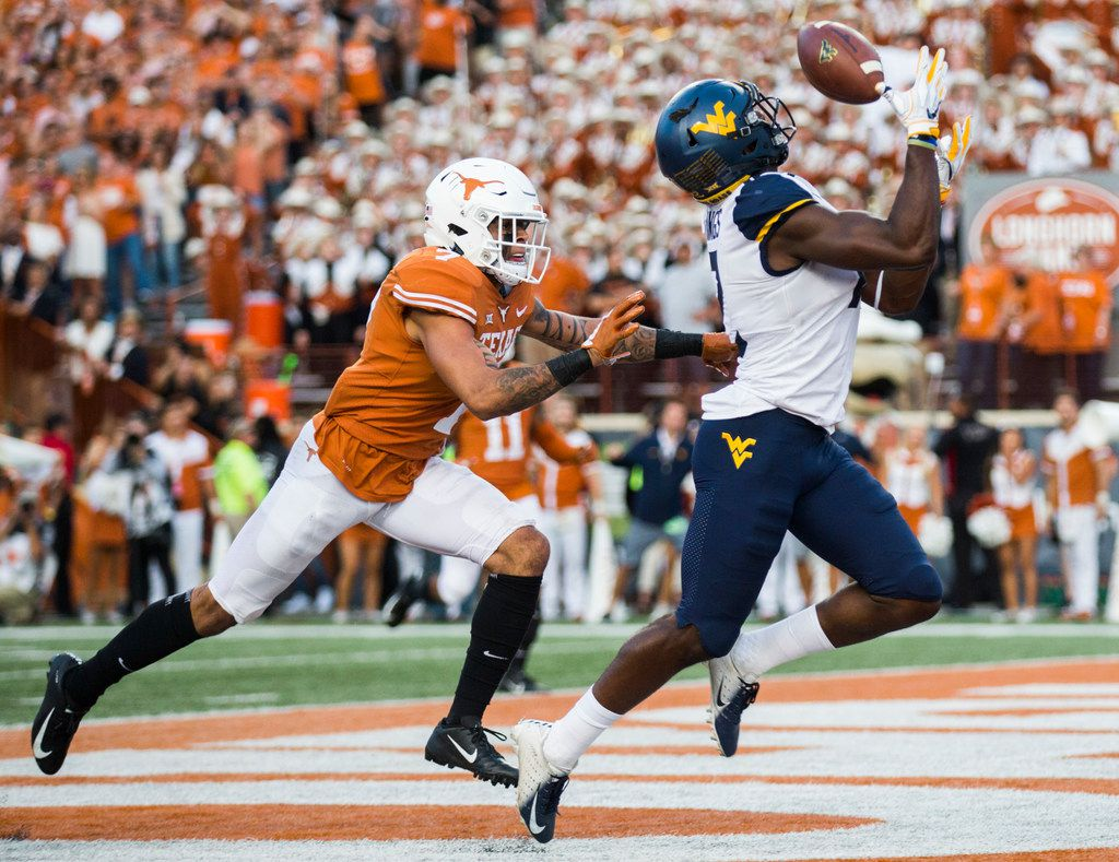West Virginia Mountaineers wide receiver Gary Jennings Jr. (12) catches a pass in the ednzone for a touchdown ahead of Texas Longhorns defensive back Caden Sterns (7) during the fourth quarter of a college football game between the University of Texas and West Virginia on Saturday, November 3, 2018 at Darrell Royal Memorial Stadium in Austin, Texas. This touchdown and a two point conversion secured the 42-41 win for West Virginia. (Ashley Landis/The Dallas Morning News)