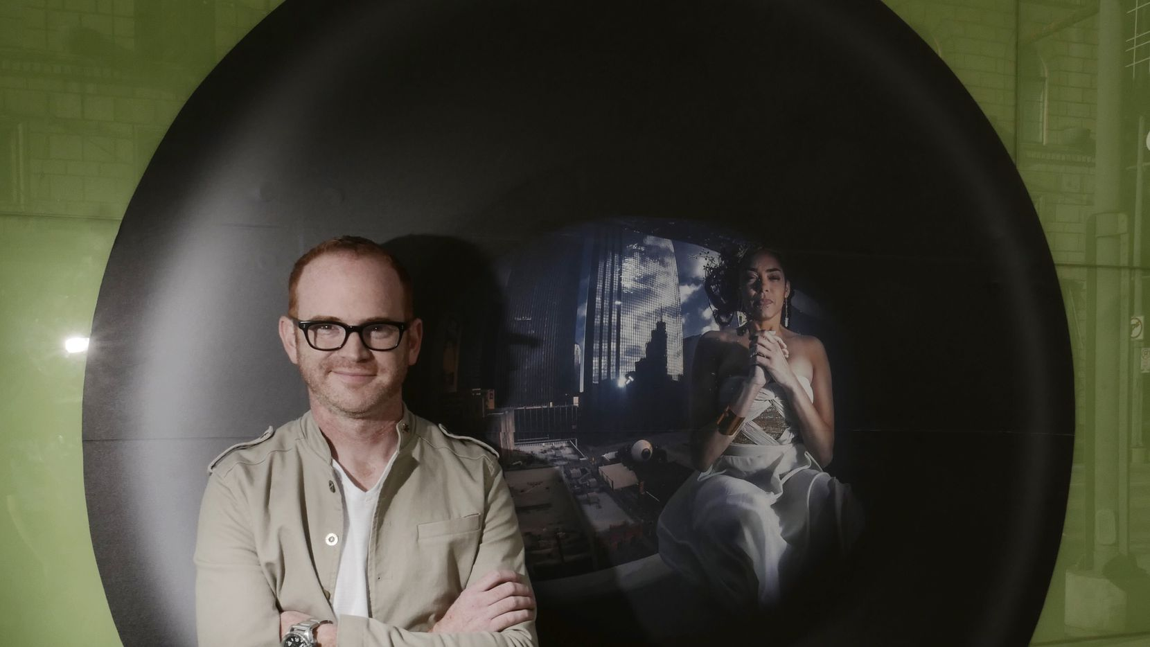 Jeremy McKane, a Dallas-based underwater fashion photographer, with his  Earth Day 2015 installation at Main Street Garden. The photo was printed on a weather-proof adhesive material and mounted on the Main Street side of the  City Park Cafe. The photo will be on display through May 22.