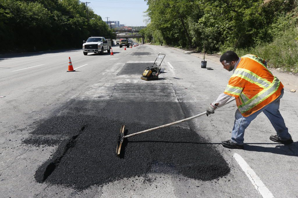 Dallas Street Services employee Gary Langley works to fix a road on Harry Hines Boulevard.
