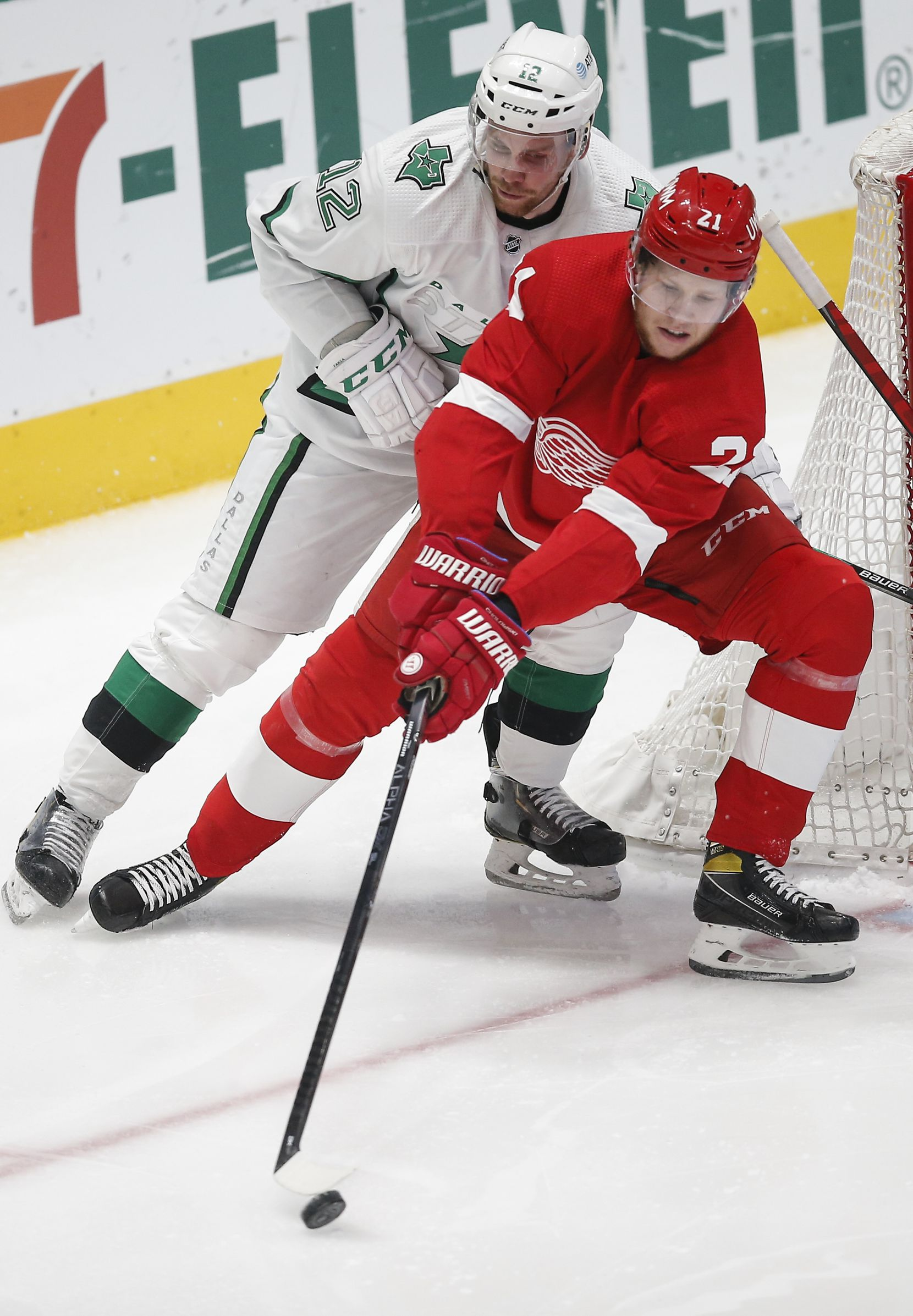 Dallas Stars forward Radek Faksa (12) and Detroit Red Wings defenseman Dennis Cholowski (21) battle for the puck during the second period of an NHL hockey game in Dallas, Monday, April 19, 2021. (Brandon Wade/Special Contributor)