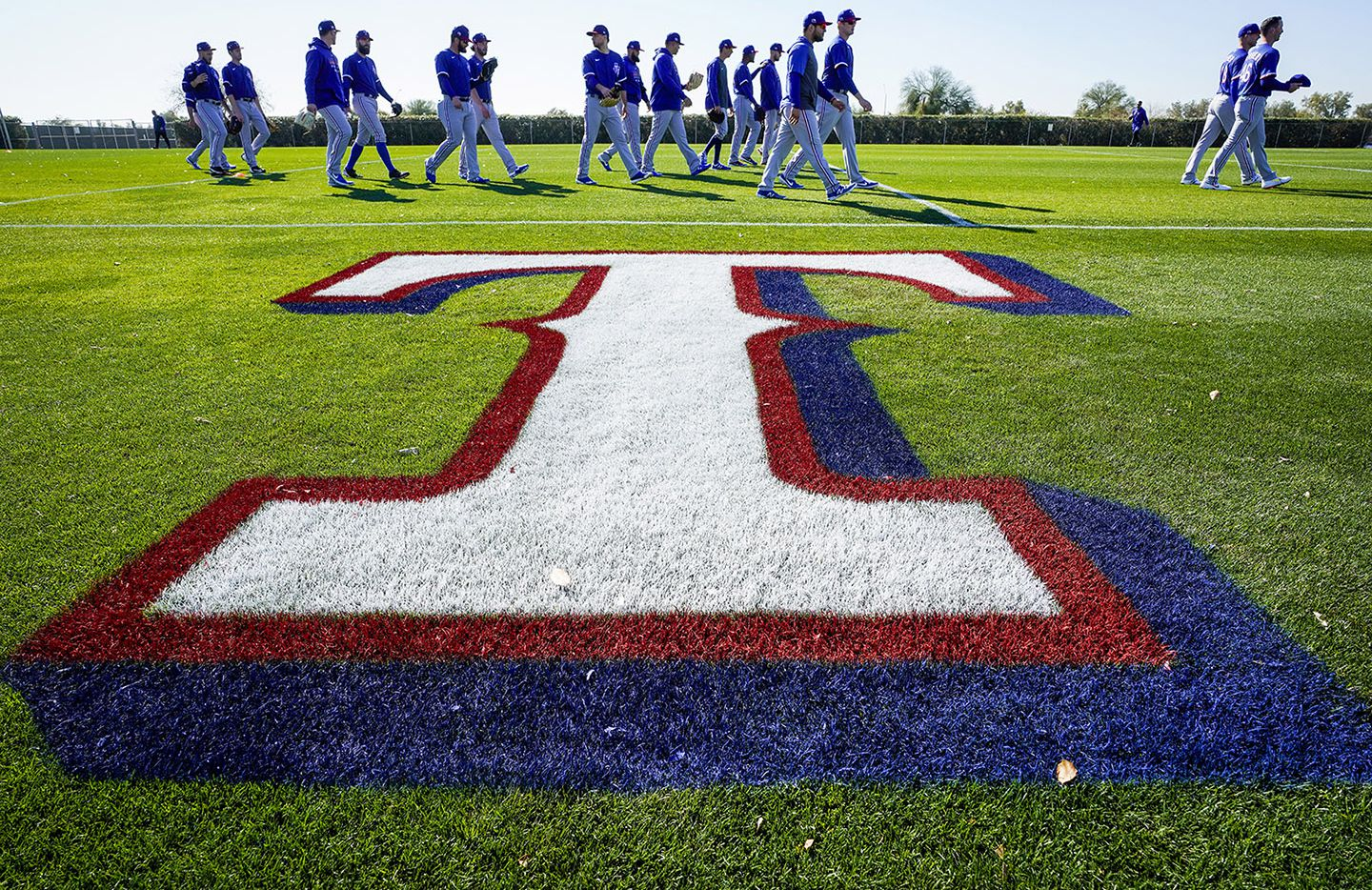 Texas Rangers players head to their first drills during the first spring training workout for pitchers and catchers at the team's training facility on Wednesday, Feb. 12, 2020, in Surprise, Ariz.