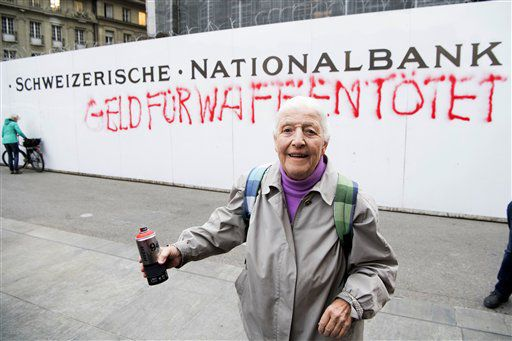 """a activista de 86 años Louise Schneider posa para la prensa tras pintar con aerosol la frase """"El dinero para armas mata"""" en una pared exterior del banco Nacional de Suiza en Berna el martes 11 de abril del 2017, como parte de una campaña para eliminar el financiamiento estatal de vendedores de armas.  (Anthony Anex/Keystone via AP)"""