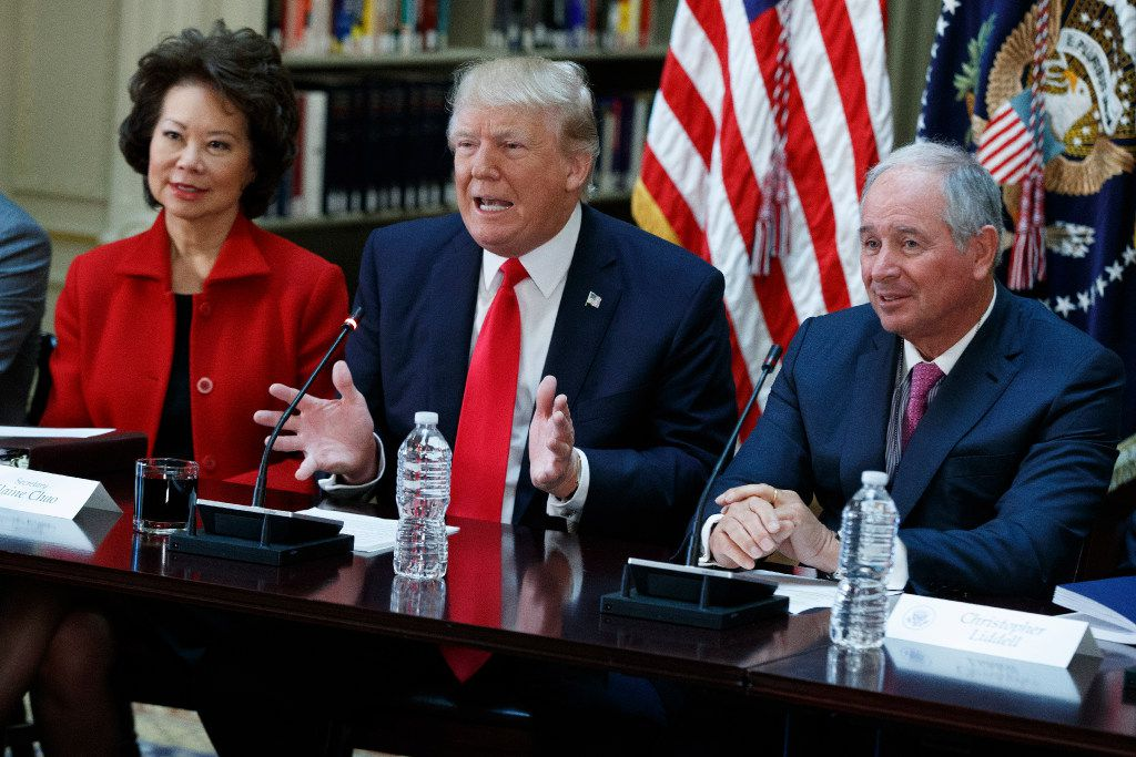 President Donald Trump, flanked by Transportation Secretary Elaine Chao and Blackstone Group CEO Stephen Schwarzman, speaks during a meeting with business leaders in the State Department Library of the Eisenhower Executive Office Building on the White House complex in Washington, Tuesday, April 11, 2017. (AP Photo/Evan Vucci)