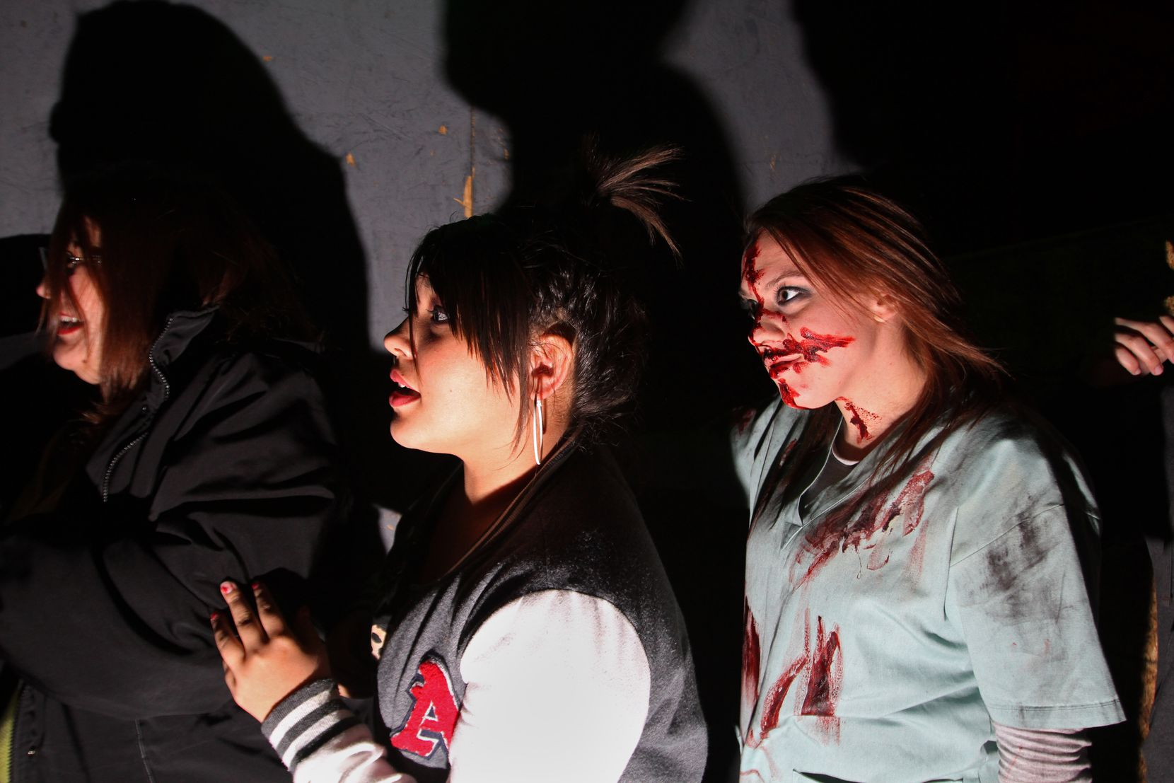 A nervous Angela Martinez (left) and Maya Martinez (center) anxiously look for what awaits them while followed by a haunted house actor, inside the Moxley Manor Haunted House in Bedford in 2012.