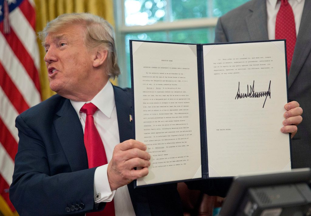 President Donald Trump holds up the executive order he signed to end family separations at the border, during an event in the Oval Office of the White House in Washington on Wednesday.