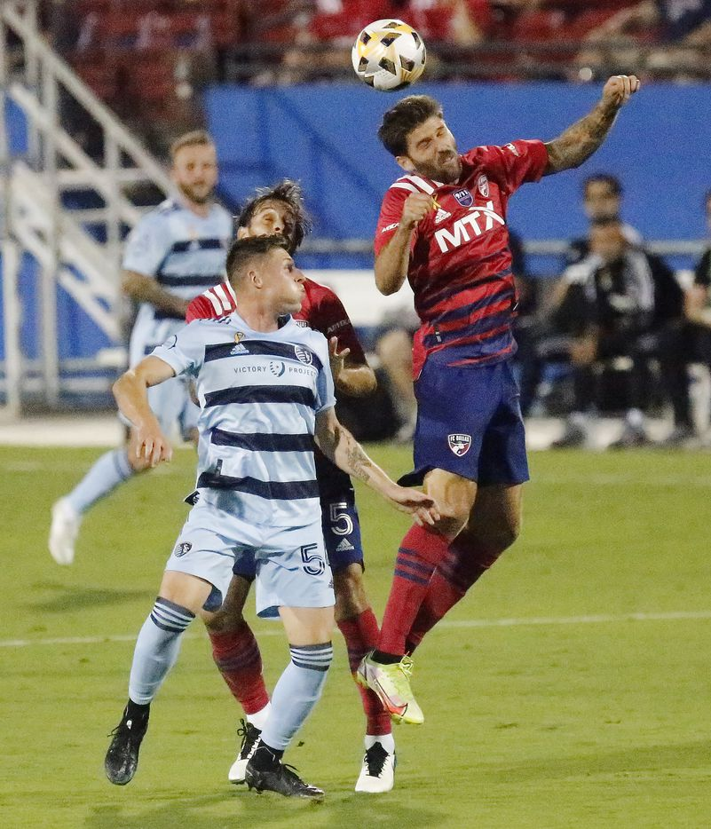 FC Dallas midfielder Ryan Hollingshead (12) gets a header above Sporting Kansas City midfielder Remi Walter (54) during the first half as FC Dallas hosted Sporting Kansas City at Toyota Stadium in Frisco on Wednesday, September 29, 2021. (Stewart F. House/Special Contributor)