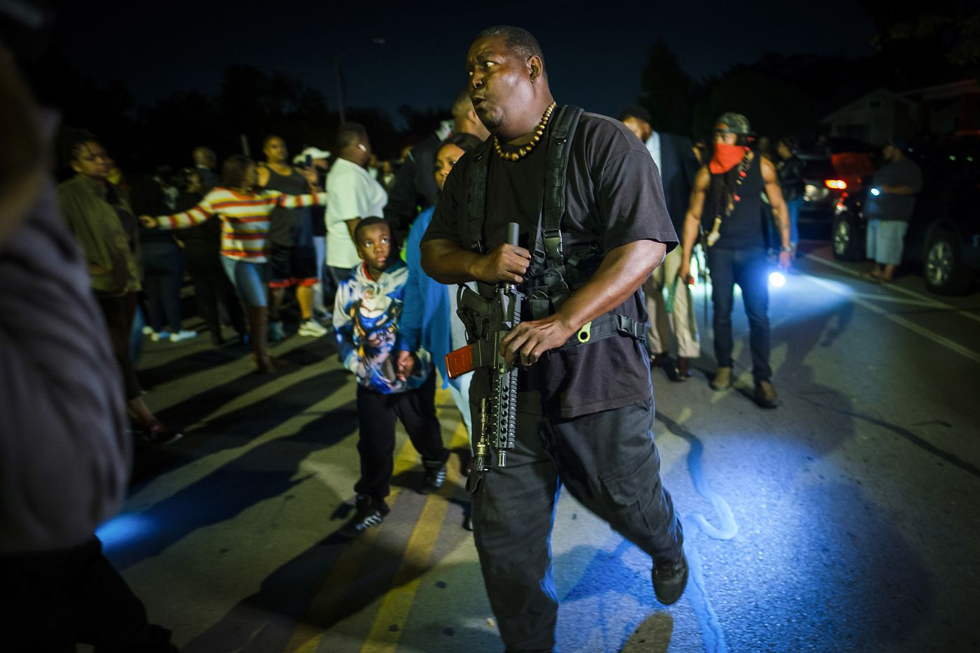 An armed man escort members of the victimÕs family from a community vigil for Atatiana Jefferson on Sunday, Oct. 13, 2019, in Fort Worth.
