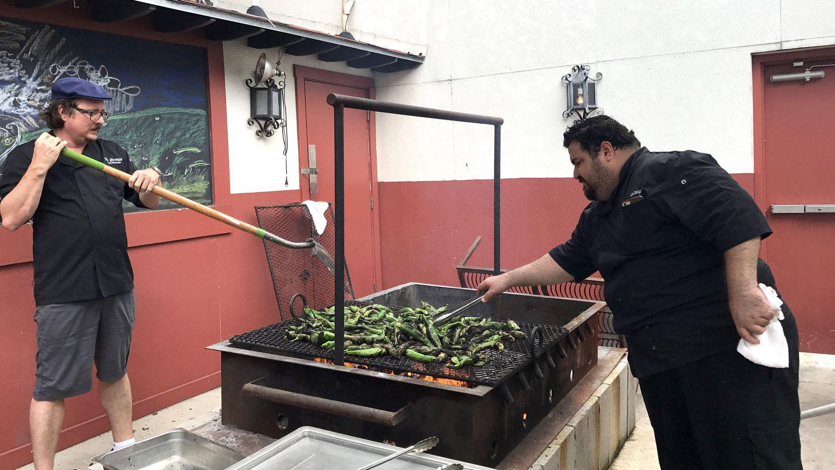 Luis Domínguez (derecha) junto aTim Byres asando chiles.