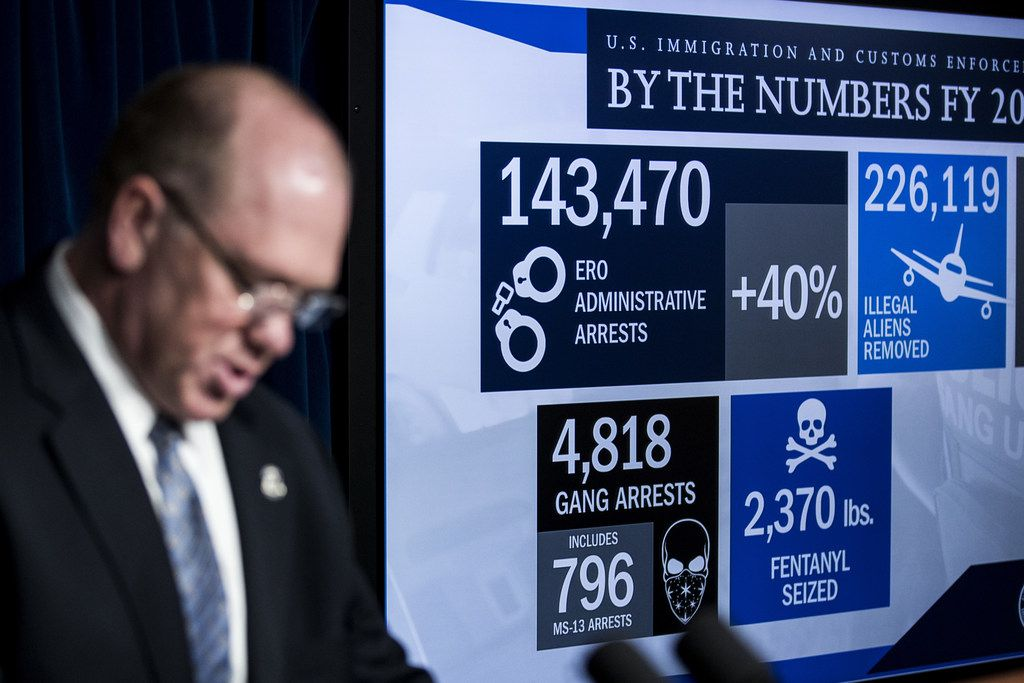 WASHINGTON, DC - DECEMBER 5: End of year statistics are displayed on a monitor as Thomas Homan, Senior Official Performing the Duties of the Director of Immigration and Customs Enforcement (ICE), speaks during a Department of Homeland Security press conference to announce end-of-year numbers regarding immigration enforcement, border security and national security, December 5, 2017 in Washington, DC. (Photo by Drew Angerer/Getty Images)