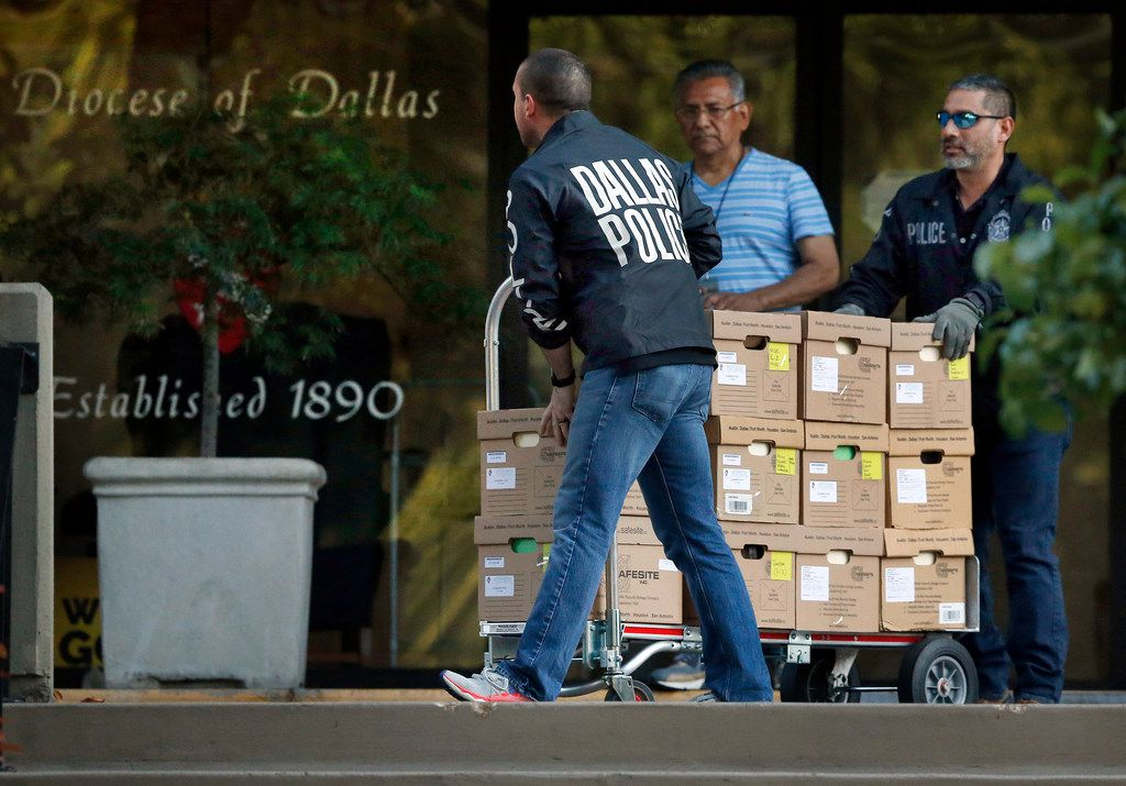 Dallas police officials cart out boxes from a raid on the Catholic Diocese of Dallas on May 15.