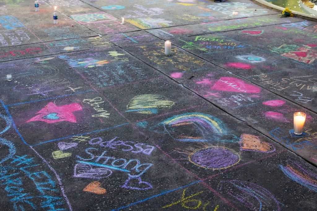 A sidewalk is filled with chalk messages following a prayer service, Sunday, Sept. 1, 2019, in Odessa, Texas, for the victims of a shooting spree the day before.