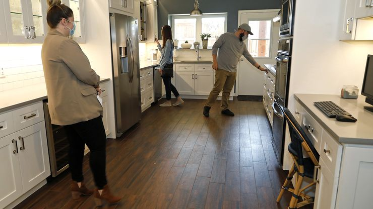 Mackenzie Larch (left), a Realtor with Ebby Halliday, looks on as Kelsey Hand (center) and her husband Steven from Champaign, Ill., check out the kitchen at an open house at 1600 Commerce Drive in Plano on Thursday.
