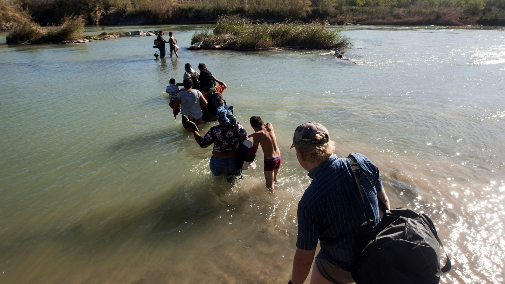 In this 2019 photo, Central American migrants try to cross the Rio Bravo from Piedras Negras, in Coahuila state, Mexico, to the city of Eagle Pass. Unauthorized border crossings plunged from 945,000 in 2000 to 210,000 in 2016, according to the Center for Migration Studies.