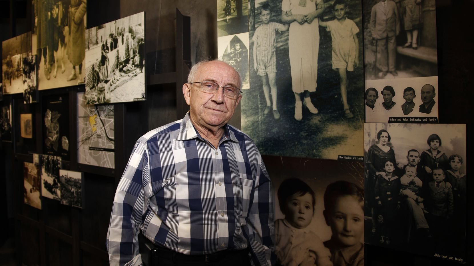 Max Glauben stands in front of some of the photographs taken of him and his mother and brother in Poland at the Dallas Holocaust Museum. (2014 File Photo/David Woo)