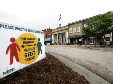 In McKinney's town square, a sign promotes social distancing. The mayor this week ordered that businesses require employees and customers to wear masks to help prevent the spread of COVID-19.
