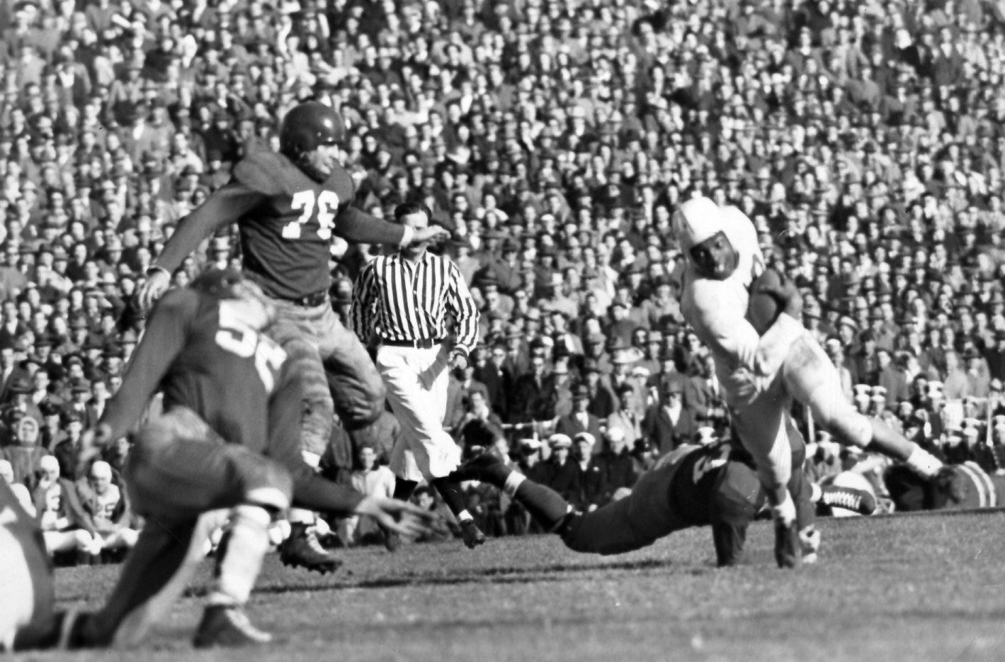 Penn State running back Wallace Triplett avoids an SMU tackler in the 1948 Classic. Triplett was one of two black players for the Nittany Lions making the 1948 Classic the first integrated football game in Texas.