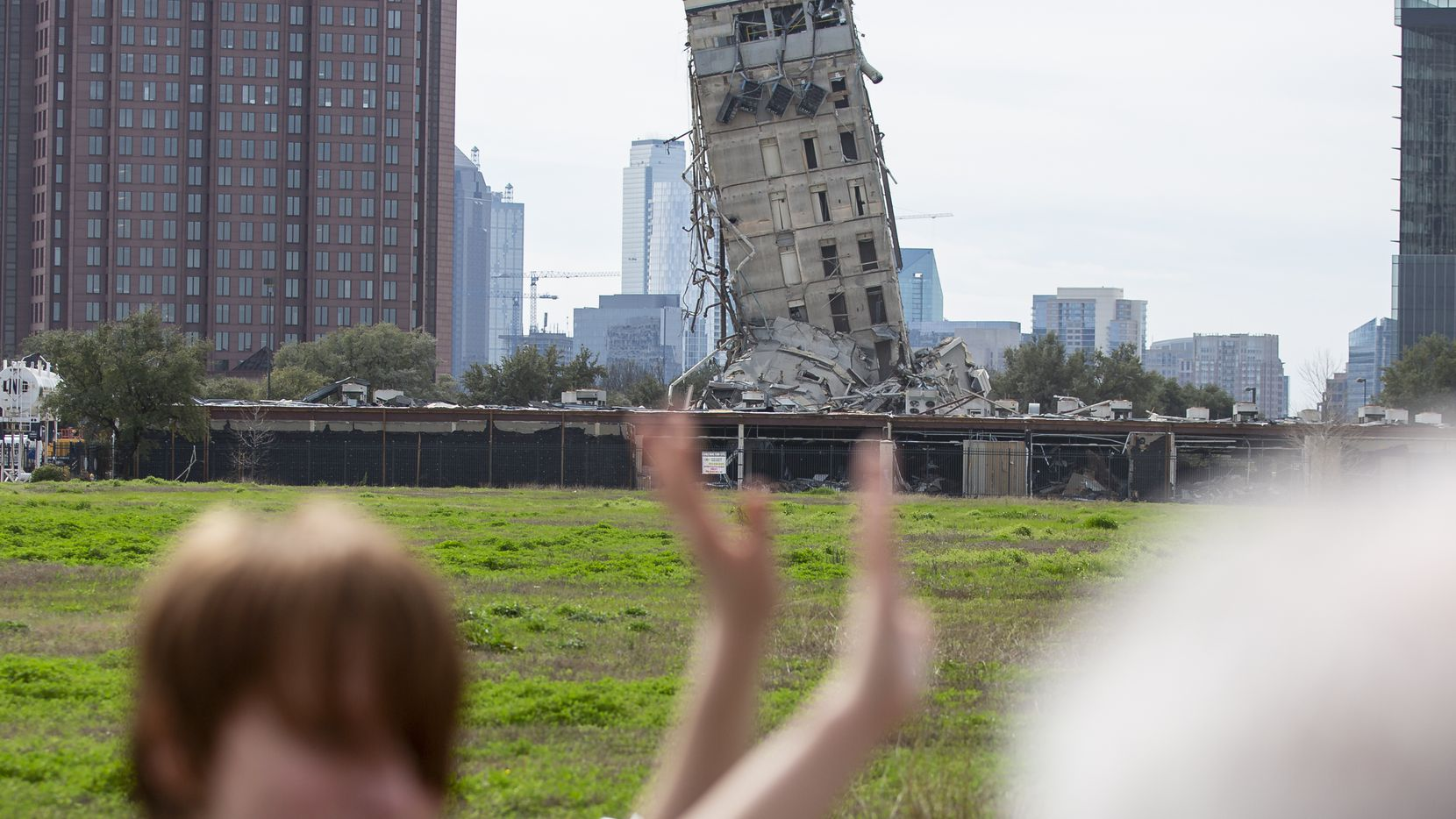 Randy Gibson takes a photo of his son Andrew, 11, in front of the 'Leaning Tower of Dallas' on Feb. 17, 2020 in Dallas. A demolition of the former Affiliated Computer Services tower on Sunday morning left the central core behind. (Juan Figueroa/ The Dallas Morning News)