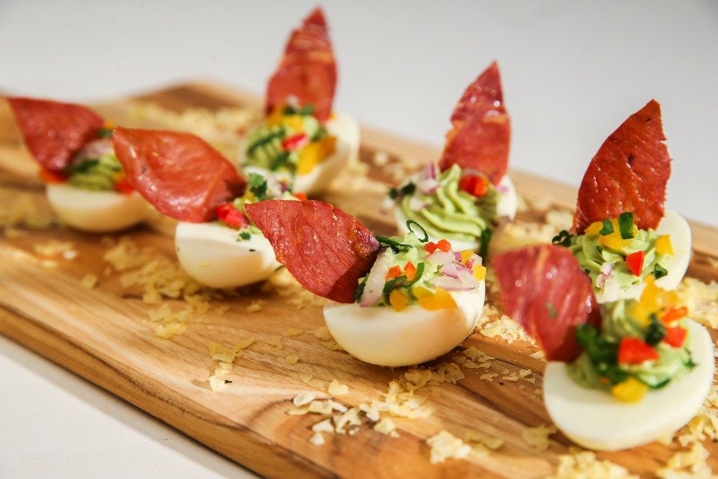 Avocado stuffed deviled eggs topped with baked prosciutto leaves