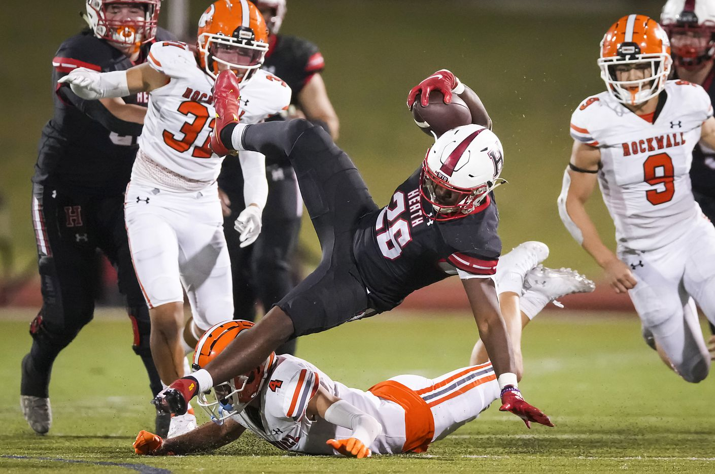 Rockwall-Heath running back  Zach Evans (26) is knocked off his feet by Rockwall defensive back Tre Carter (4) during the second half of a District 10-6A high school football game at Wilkerson-Sanders Stadium on Friday, Sept. 24, 2021, in Rockwall.  Rockwall-Heath won the game 79-71 in double overtime.