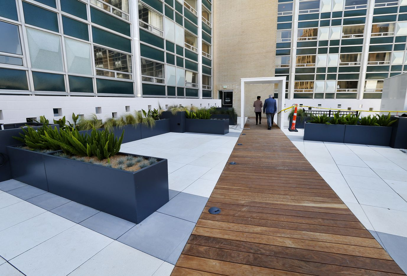 A wooden boardwalk leads to and from the pool area on the fourth floor at the Statler Residences in downtown Dallas.