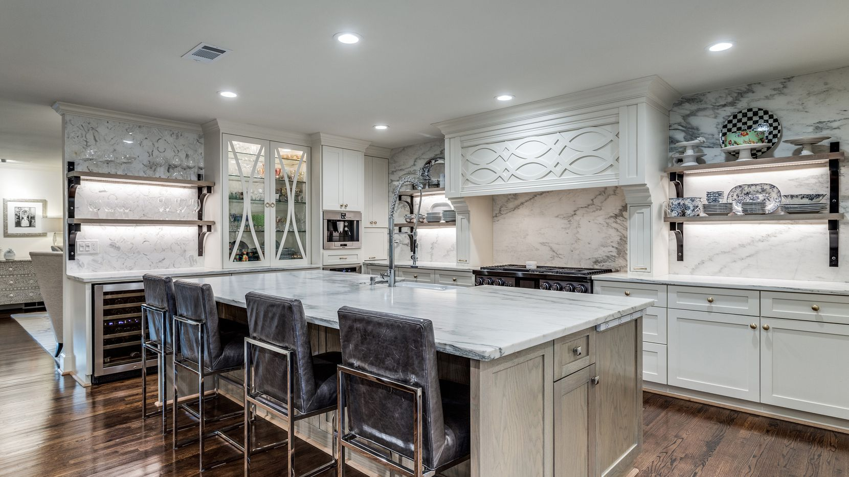 The transitional farmhouse home at 8302 Midway Road in Bluffview Estates features a kitchen with a white marble island and a pantry. It opens to the family room.