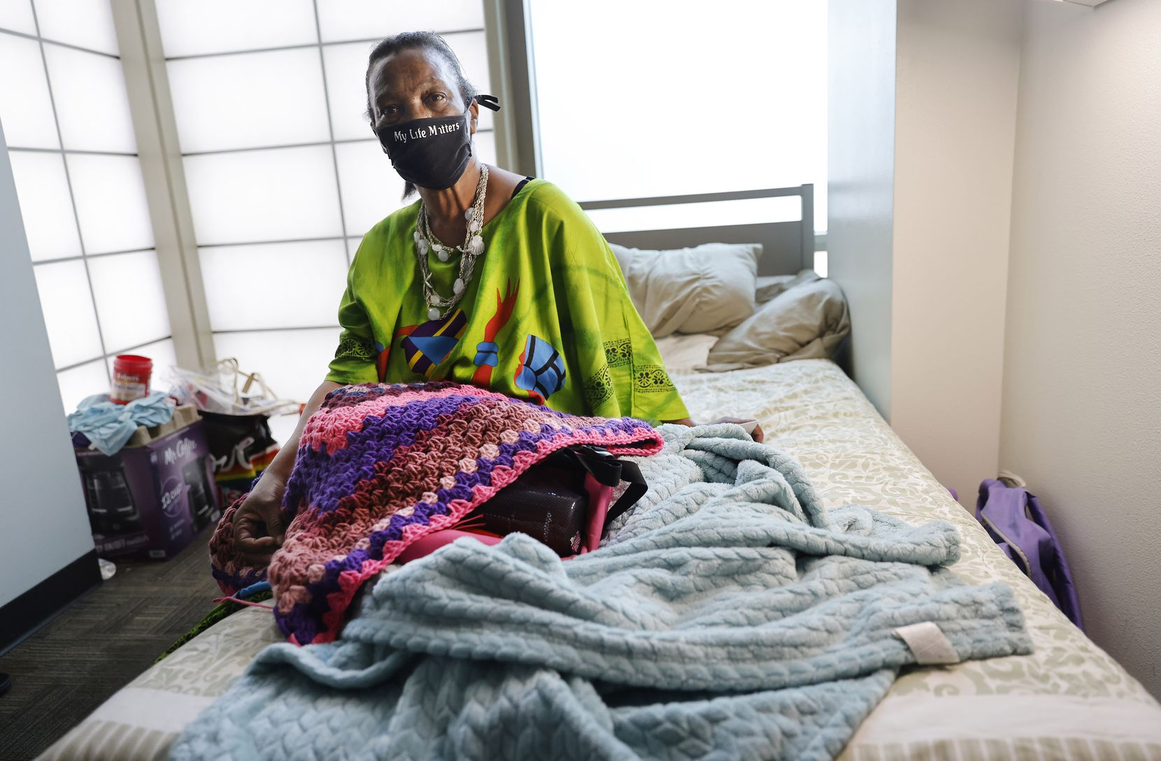 Patricia Freeman, 65, found her way to The Bridge Homeless Recovery Center in downtown Dallas earlier this year after nearly freezing to death at a Houston bus stop during February's deadly storm. She plans to get settled into a more permanent place through rapid rehousing with the assistance of her case manager, Amanda Crowe. Patricia is photographed in her transitional room with a blanket she is crocheting at The Bridge,