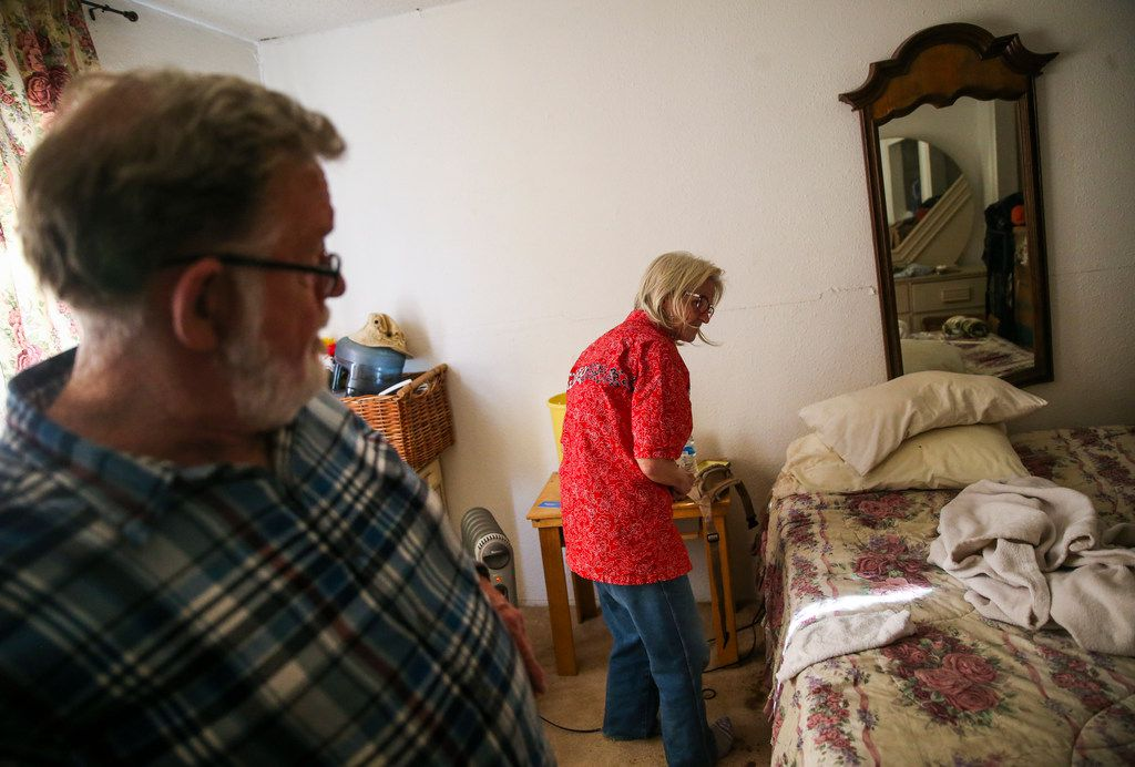 Gerald Miller (left) checks on his roommate Cheryl Embrey at their home in Bryan Song Apartments.
