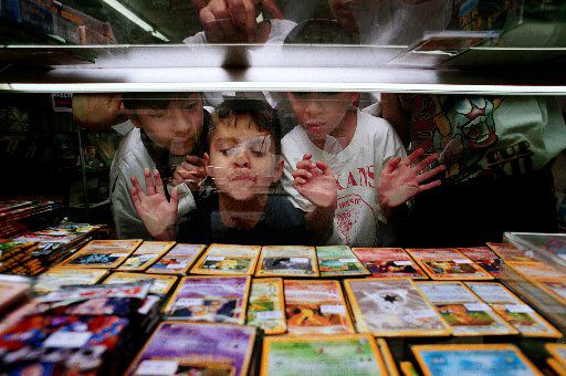 Larry Lopez, 11, John Armijo, 4, and Jaime Lopez, 10, look at rare Pokemon cards through a glass case at Cosmic Comics in Grand Prairie in 2000.