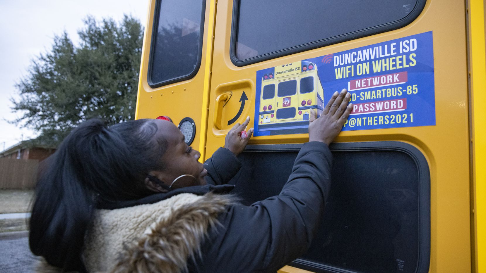 Duncanville ISD bus driver Stephanie Brown posts the network name and password on the Wi-Fi-equipped school bus parked outside the Renaissance Village apartment complex in Duncanville.