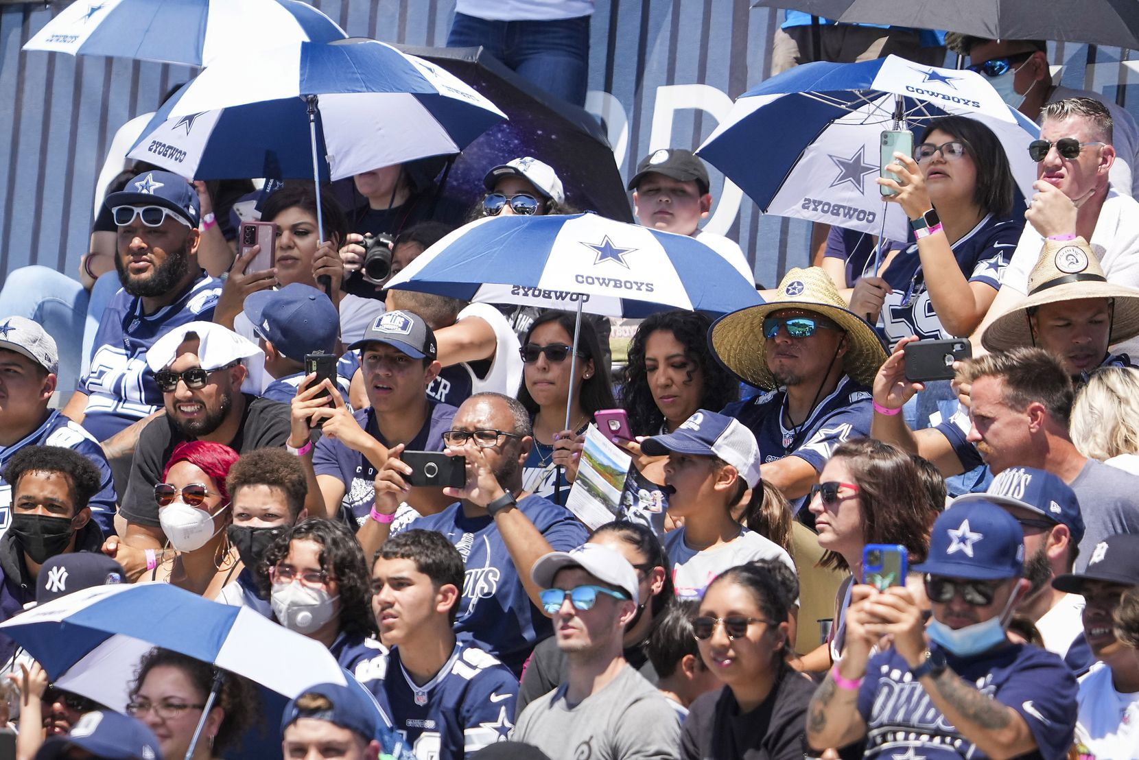Dallas Cowboys fans use umbrellas for shade as they watch a practice at training camp on Sunday, Aug. 1, 2021, in Oxnard, Calif. (Smiley N. Pool/The Dallas Morning News)