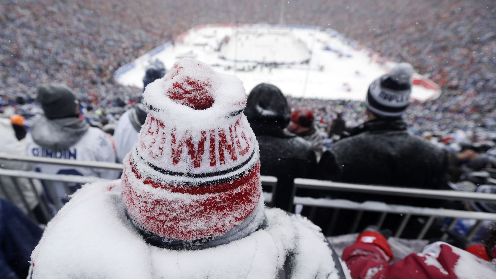 A Detroit Red Wings fan, coated with snow, watched during the third period of the 2014 Winter Classic in Ann Arbor, Mich. In all probability, Dallas Stars fans won't have to worry about a scene like this at the Cotton Bowl on Jan. 1 for this season's version of the outdoor hockey game.